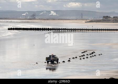 Man collecting sea coal, Seaton Carew, Hartlepool, England, UK - Stock Photo