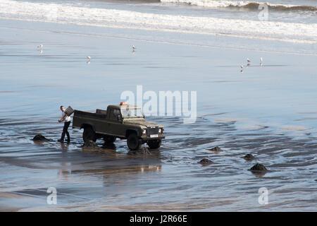 Man collecting sea coal at Seaton Carew, Hartlepool, England, UK - Stock Photo