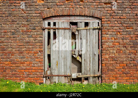 an old weathered barn door with broken wood and rusty hinges in a red brick farm outbuilding - Stock Photo