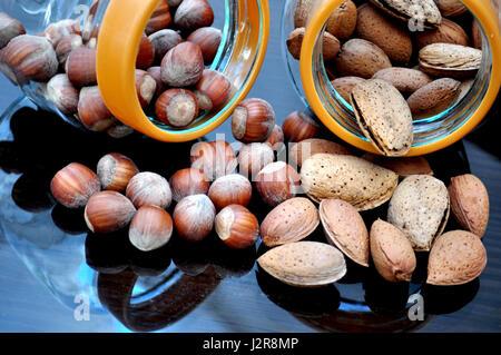 Glass jar with almonds and hazelnuts - Stock Photo