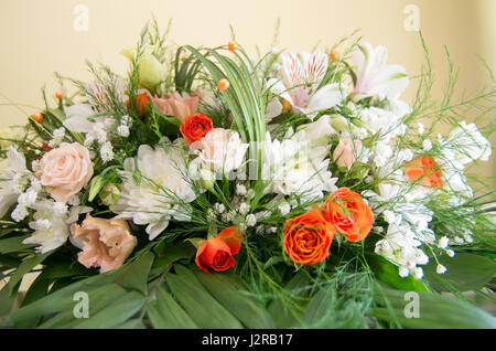 Fresh and fragrant flowers arranged with decorative leaves and grasses - Stock Photo