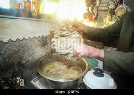 An old man boiling pork meat on the stove and holding a piece of ribs. - Stock Photo