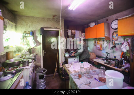 An old man cooking on the stove in an obsolete rustic kitchen. - Stock Photo