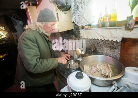 An old man boiling pork meat on the stove. - Stock Photo