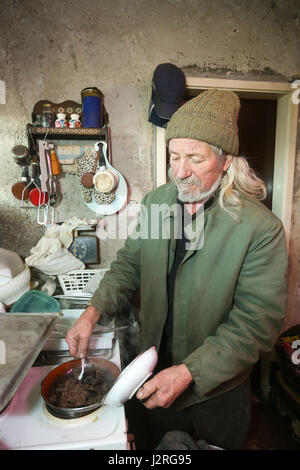 An old man cooking meat on stove in kitchen. - Stock Photo