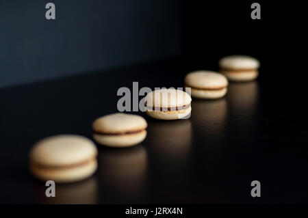Macaroons with chocolate cream ordered in line - Stock Photo