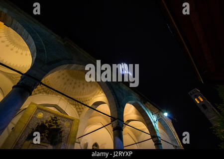 Gazi Husrev Begova mosque in Sarajevo in the evening. The Sarajevo bazar clock tower can be seen in the background. - Stock Photo