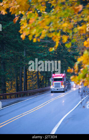 Classic red semi truck on a beautiful autumn wet from the rain straight road with the reflection of headlights on - Stock Photo