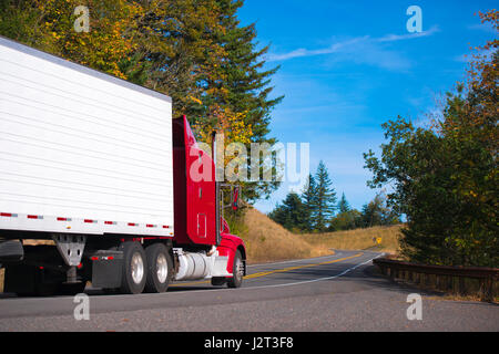 Classic red big rig long haul semi truck transporting cargo in refer trailer on a beautiful autumn winding devided - Stock Photo