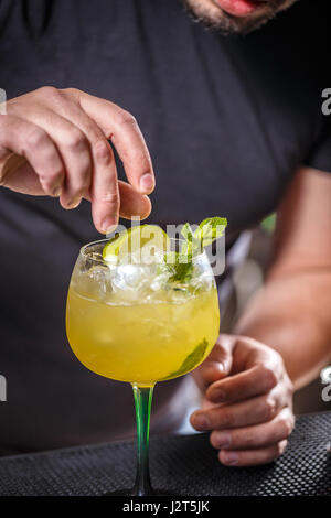 Bartender putting lime into glass, barman is decorating cocktail - Stock Photo