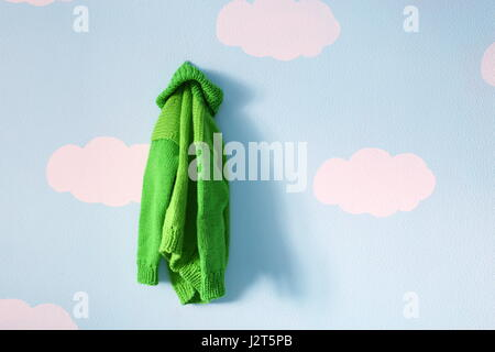 knitted baby sweater hanging on blue wall - Stock Photo