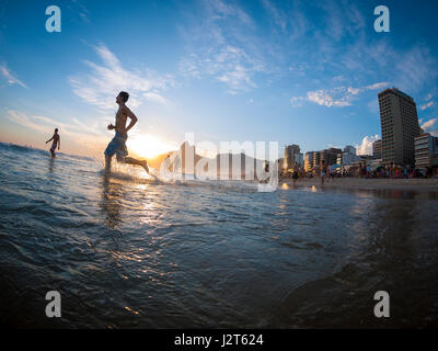RIO DE JANEIRO - FEBRUARY 2, 2013: Silhouettes pass in front of the sunset on the shore of Ipanema Beach. - Stock Photo