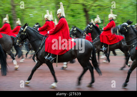 LONDON - MAY 18, 2016: Mounted regiment of Queen's Guards in red coats pass in motion blur on the Mall during a - Stock Photo