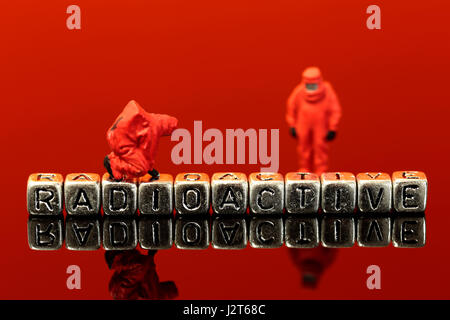Miniature scale model team in chemical suits with the word radioactive on beads - Stock Photo