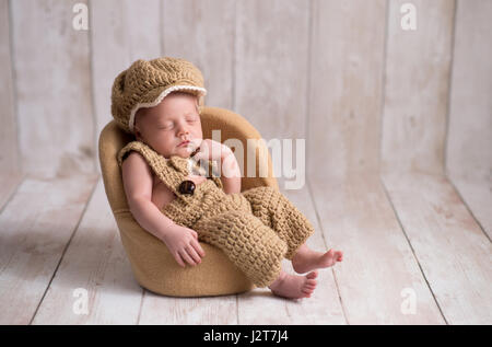 Nine day old, newborn baby boy wearing a crocheted, little man suit with newsboy cap and bowtie. He is sleeping - Stock Photo