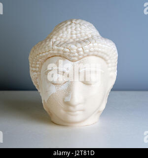 Buddha face. Buddha statue made of white marble. Concept of peace, calm and tranquility. Buddhist artifact for Zen style interior decor.
