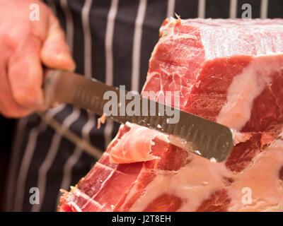Horizontal close up of a butcher slicing a Serrano Ham. - Stock Photo