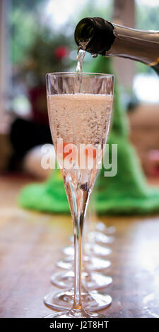 Vertical close up view of champagne flutes being filled up with alcohol. - Stock Photo