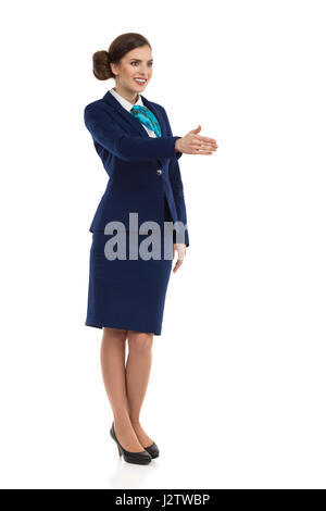 Young woman in blue formalwear and high heels, standing and giving hand for a handshake. Front side view. Full length - Stock Photo