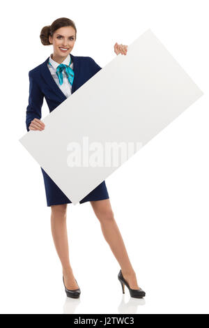 Young woman in blue formalwear and high heels, holding blank placard and smiling. Front view. Full length studio - Stock Photo