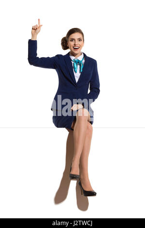 Smiling woman in blue suit and skirt, sitting on a top, looking at camera and pointing up. Full length studio shot. - Stock Photo