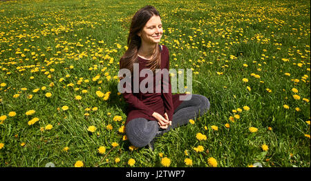 Beautiful young woman relaxing on a meadow with many dandelions in the spring sun. Smiling with copyspace. - Stock Photo