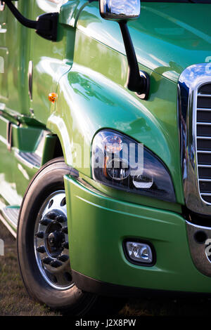 Sunlit powerful modern stylish and comfortable green big rig semi truck the latest model of commercial long-distance - Stock Photo