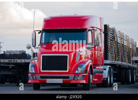 Powerful bright red semi truck with low cabin with modern accessories in stainless steel with a flat bed trailer, - Stock Photo