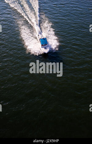 Fast motor boat with white blue canopy rushes through the dark surface of the river, raising the waves, leaving - Stock Photo