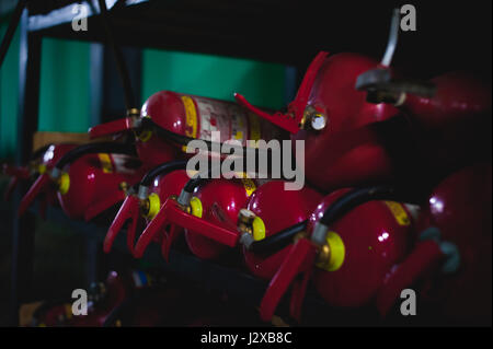 Many fire extinguishers lie on the rack - Stock Photo