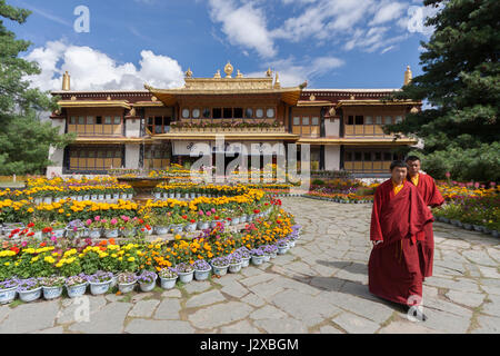 Two young Tibetan Buddhist monks walking in front of Norbulingka The Summer Palace in Lhasa, Tibet - Stock Photo