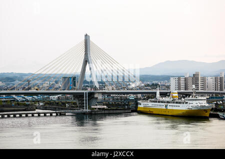 seaside view of cable-stayed aomori bay bridge with memorial ship 'Hakkoda-Maru', floating museum, in foreground. - Stock Photo