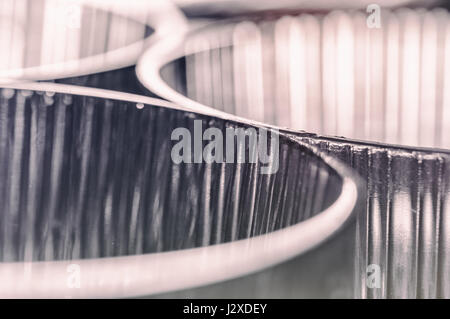A soft, monochrome macro photograph of curving glass dishes - Stock Photo