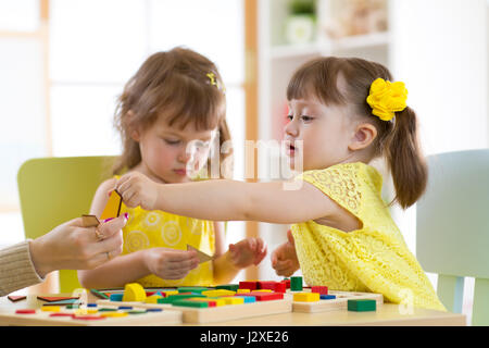 Preschool teacher and children playing with educational sorter toys in classroom - Stock Photo