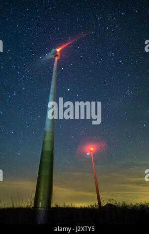 Tall wind turbines under night, starry sky, Dulsk, Poland. Part of windmill farm. - Stock Photo