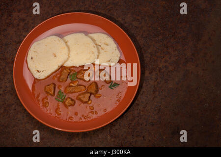 Traditional hungarian goulash wit dumplings on plate on rusty metal sheet. - Stock Photo