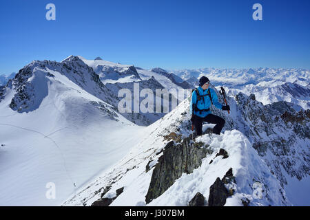Female back-country skier ascending to Zwerchwand, Realspitze and Olperer in background, Zillertal, Zillertal Alps, - Stock Photo