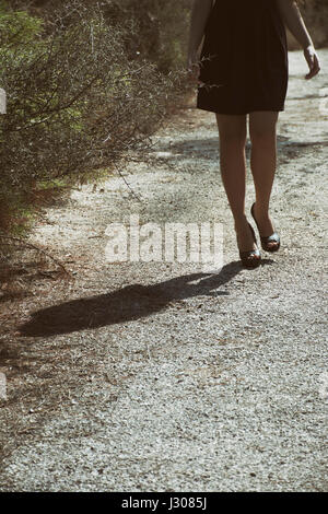 Close up of a young woman's legs walking on a countryside road - Stock Photo
