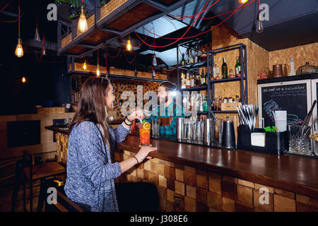 A girl with  cocktail smiles behind counter at the bar - Stock Photo