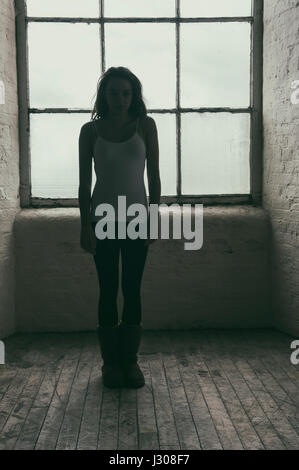 Young woman standing near the window - Stock Photo