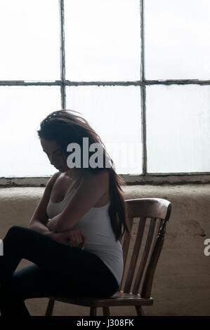 Sad young woman sat on chair near the window - Stock Photo