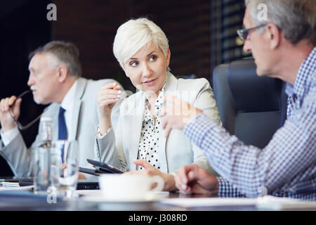 Group of business people huddled around table working - Stock Photo