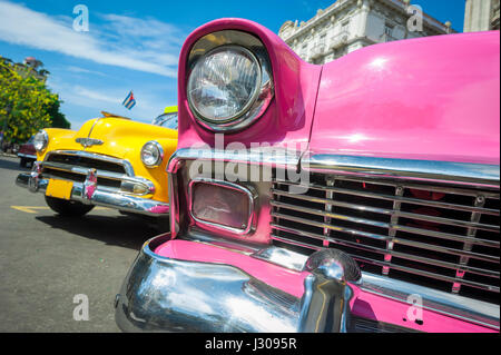 HAVANA - JUNE, 2011: Brightly colored American cars serving as taxis stand parked on the street in Centro. - Stock Photo