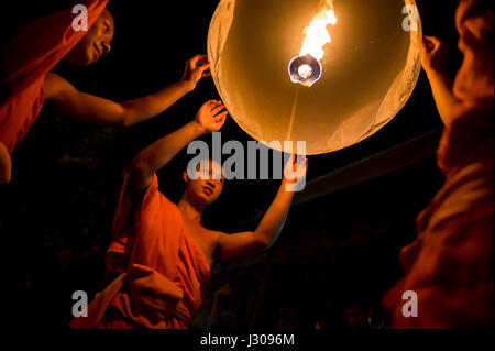 CHIANG MAI, THAILAND - NOVEMBER 7, 2014: Young Buddhist monks in orange robes launch sky lanterns at the annual - Stock Photo