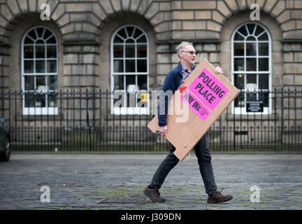Polling logistics officer Roy Drury carries a polling station sign from Lothian Chambers in Edinburgh, as election - Stock Photo