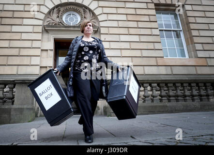 Polling station staff trainer Julie Wright carries ballot boxes and signs from Lothian Chambers in Edinburgh, as - Stock Photo