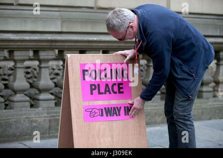 Polling logistics officer Roy Drury secures a polling station sign from Lothian Chambers in Edinburgh, as election - Stock Photo
