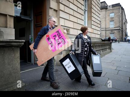 Polling logistics officer Roy Drury and polling station staff trainer Julie Wright collect ballot boxes and signs - Stock Photo
