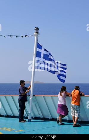 crew raising greek flag on board of a ferry - Stock Photo