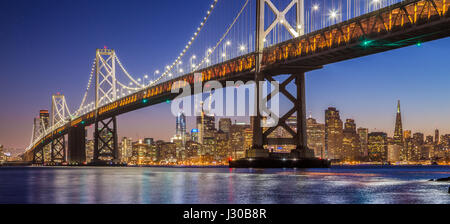 Classic panoramic view of famous Oakland Bay Bridge with the skyline of San Francisco illuminated in beautiful post - Stock Photo
